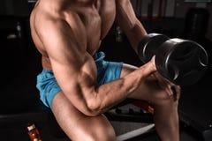 Πολύ ο αθλητικός τύπος δύναμης bodybuilder εκτελεί την άσκηση με τους αλτήρες στη σκοτεινή γυμναστική Στοκ φωτογραφίες με δικαίωμα ελεύθερης χρήσης