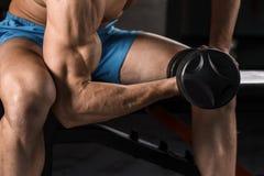 Πολύ ο αθλητικός τύπος δύναμης bodybuilder εκτελεί την άσκηση με τους αλτήρες στη σκοτεινή γυμναστική Στοκ Εικόνες