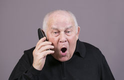 Πολύ συναισθηματικό άτομο με τις κραυγές τηλεφωνικών μικροτηλεφώνων σε ένα γκρίζο υπόβαθρο Στοκ Εικόνες