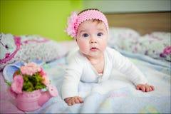 Πολύ χαριτωμένο μικρό κορίτσι που βρίσκεται στο κρεβάτι, που κλίνει στη λαβή στοκ εικόνα