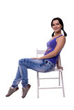 Πολύ όμορφη νέα γυναίκα με μια ντροπαλή συνεδρίαση ουρών σε μια καρέκλα που απομονώνεται λοξά στο άσπρο υπόβαθρο Στοκ εικόνα με δικαίωμα ελεύθερης χρήσης