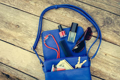 Πράγματα από το ανοικτό γυναικείο πορτοφόλι Τα καλλυντικά, τα χρήματα και τα εξαρτήματα γυναικών ` s έπεσαν από την μπλε τσάντα Στοκ εικόνα με δικαίωμα ελεύθερης χρήσης