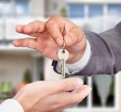Πράκτορας ιδιοκτησίας που δίνει τα κλειδιά στον ιδιοκτήτη ενάντια στο καινούργιο σπίτι Στοκ φωτογραφίες με δικαίωμα ελεύθερης χρήσης