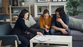 Πράκτορας κατοικίας που παρουσιάζει σχέδια σπιτιών στο όμορφο ζεύγος που μιλά στο εσωτερικό στο σπίτι φιλμ μικρού μήκους