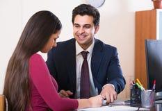 Πράκτορας που ακούει τον πελάτη και που χαμογελά στην αντιπροσωπεία Στοκ Εικόνες