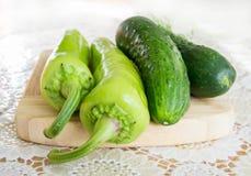 Πράσινα αγγούρια και πράσινα πιπέρια σε ένα ξύλινο πιάτο και μια διακοσμημένη κάλυψη - μπροστινή άποψη Στοκ φωτογραφία με δικαίωμα ελεύθερης χρήσης