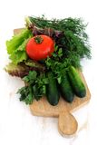 Πράσινα αγγούρια, ντομάτα και φρέσκα χορτάρια Στοκ Εικόνα