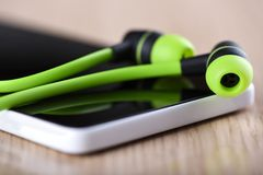 Πράσινα ακουστικά στην οθόνη smartphone Εστίαση στα ακουστικά στοκ εικόνες