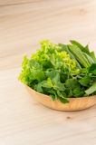 Πράσινα λαχανικά στο ξύλινο πιάτο στο ξύλινο υπόβαθρο Στοκ εικόνα με δικαίωμα ελεύθερης χρήσης