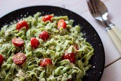 Πράσινα ζυμαρικά με τις ντομάτες και το τυρί παρμεζάνας στοκ εικόνα