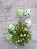 Πράσινα και άσπρα αυγά Πάσχας και άσπρη άγρια ανθοδέσμη λουλουδιών Στοκ Εικόνες