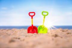 Πράσινα και κόκκινα πλαστικά φτυάρια στην παραλία Στοκ Φωτογραφία