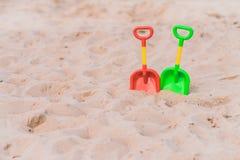 Πράσινα και κόκκινα πλαστικά φτυάρια στην παραλία Στοκ φωτογραφία με δικαίωμα ελεύθερης χρήσης