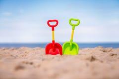 Πράσινα και κόκκινα πλαστικά φτυάρια στην παραλία Στοκ εικόνα με δικαίωμα ελεύθερης χρήσης