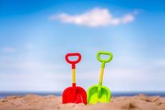 Πράσινα και κόκκινα πλαστικά φτυάρια στην παραλία Στοκ εικόνες με δικαίωμα ελεύθερης χρήσης