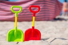 Πράσινα και κόκκινα πλαστικά φτυάρια στην παραλία Στοκ φωτογραφίες με δικαίωμα ελεύθερης χρήσης