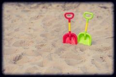 Πράσινα και κόκκινα πλαστικά φτυάρια στην παραλία Στοκ Φωτογραφίες