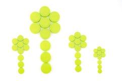 Πράσινα καλύμματα μπουκαλιών που τακτοποιούνται στη μορφή λουλουδιών Στοκ Εικόνες