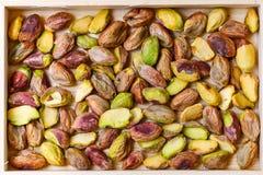 Πράσινα καρύδια φυστικιών χωρίς κοχύλι σε ένα ξύλινο κιβώτιο Στοκ εικόνες με δικαίωμα ελεύθερης χρήσης