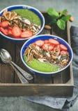 Πράσινα κύπελλα προγευμάτων καταφερτζήδων με τους σπόρους, τα καρύδια, τα φρούτα και τα μούρα Στοκ εικόνα με δικαίωμα ελεύθερης χρήσης