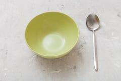 Πράσινα κύπελλο και κουτάλι στο γκρίζο συγκεκριμένο πιάτο Στοκ Εικόνες