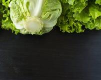 πράσινα λαχανικά Πράσινο λαχανικό στο μαύρο ξύλινο υπόβαθρο Σπανάκι, λάχανο και μαρούλι Τοπ όψη Λαχανικά στα σύνορα του imag Στοκ Φωτογραφίες