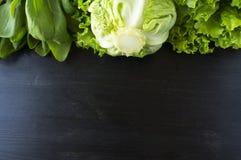 πράσινα λαχανικά Πράσινο λαχανικό στο μαύρο ξύλινο υπόβαθρο Σπανάκι, λάχανο και μαρούλι Τοπ όψη Λαχανικά στα σύνορα του imag Στοκ Εικόνες