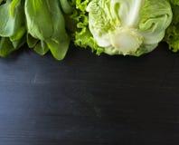 πράσινα λαχανικά Πράσινο λαχανικό στο μαύρο ξύλινο υπόβαθρο Σπανάκι, λάχανο και μαρούλι Τοπ όψη Λαχανικά στα σύνορα του imag Στοκ εικόνες με δικαίωμα ελεύθερης χρήσης