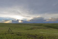 Πράσινα λιβάδια και κίτρινο ηλιοβασίλεμα μέσω των σύννεφων στοκ εικόνες