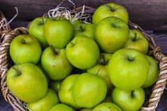 Πράσινα μήλα σε ένα καλάθι σε ένα ξύλινο υπόβαθρο Στοκ εικόνα με δικαίωμα ελεύθερης χρήσης