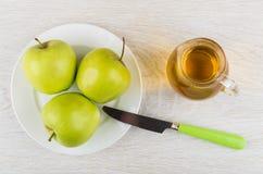 Πράσινα μήλα στο πιάτο, χυμός μήλων στην κανάτα και μαχαίρι Στοκ Εικόνα