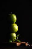 Πράσινα μήλα που κάνουν το σωρό ή τον πύργο με τον κλάδο της φρέσκιας μέντας στο μαύρο υπόβαθρο Στοκ εικόνες με δικαίωμα ελεύθερης χρήσης