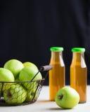 Πράσινα μήλα σε καλάθι και δύο μπουκάλια του χυμού της Apple Στοκ Εικόνα