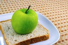 Πράσινα μήλο και ψωμί στο άσπρο πιάτο Στοκ φωτογραφία με δικαίωμα ελεύθερης χρήσης
