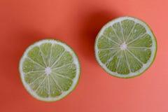 Πράσινα μισά ασβέστη στο φωτεινό πορτοκαλί υπόβαθρο στοκ φωτογραφίες με δικαίωμα ελεύθερης χρήσης
