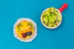 Πράσινα μούρα ακτινίδιων σε ένα κόκκινο πιάτο Κέικ με τον καρπό Στοκ φωτογραφία με δικαίωμα ελεύθερης χρήσης