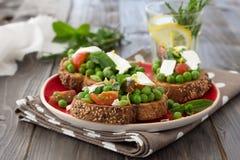 Πράσινα μπιζέλια με τις ντομάτες κερασιών, το τυρί φέτας και τη μέντα στη φρυγανιά Στοκ Εικόνα