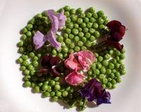 Πράσινα μπιζέλια σε ένα άσπρο υπόβαθρο, με τα λουλούδια που εξωραΐζονται στοκ φωτογραφία με δικαίωμα ελεύθερης χρήσης