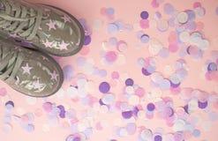 Πράσινα παπούτσια παιδιού με την τυπωμένη ύλη αστεριών στο ρόδινο υπόβαθρο με το κομφετί στοκ φωτογραφίες με δικαίωμα ελεύθερης χρήσης