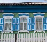Πράσινα παράθυρα σπιτιών με τα μπλε παραθυρόφυλλα Στοκ Φωτογραφίες
