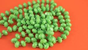 Πράσινα περιδέραια χαντρών στο πορτοκάλι που απομονώνεται φιλμ μικρού μήκους