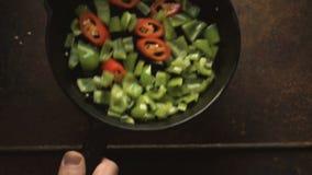 Πράσινα πιπέρι και τσίλι σε ένα τηγανίζοντας τηγάνι χυτοσιδήρων βίντεο απόθεμα βίντεο