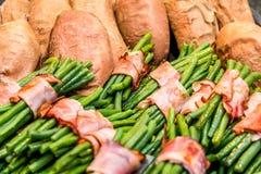 Πράσινα φασόλια που κυλιούνται στο μπέϊκον και τις ψημένες γλυκές πατάτες Στοκ Εικόνες