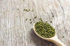 Πράσινα φασόλια στο κουτάλι στο ξύλινο πάτωμα, δημητριακά στο ξύλινο πάτωμα Στοκ Εικόνα