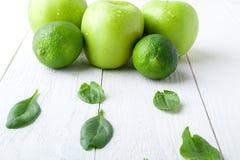 Πράσινα φρούτα στο άσπρο ξύλινο υπόβαθρο Apple, ασβέστης, σπανάκι detox τρόφιμα υγιή Στοκ Εικόνα