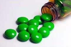 Πράσινα χάπια με ένα καφετί μπουκάλι Στοκ εικόνα με δικαίωμα ελεύθερης χρήσης