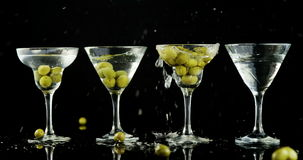 Πράσινες ελιές που πέφτουν σε τέσσερα γυαλιά κοκτέιλ απόθεμα βίντεο