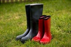 Πράσινες και κόκκινες μπότες κηπουρικής στη μακριά χλόη Στοκ φωτογραφίες με δικαίωμα ελεύθερης χρήσης