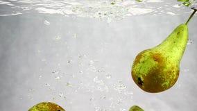 Πράσινες πτώσεις αχλαδιών στο νερό με πολλές μικρές φυσαλίδες Βίντεο των φρούτων στο απομονωμένο άσπρο υπόβαθρο φιλμ μικρού μήκους