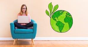 Πράσινη γη με τη νέα γυναίκα που χρησιμοποιεί το lap-top της Στοκ Φωτογραφία